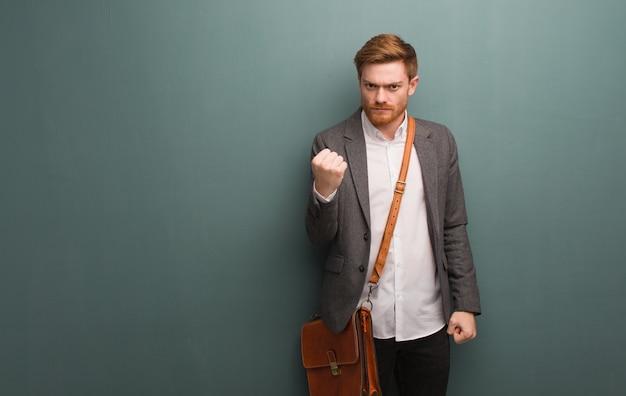 Giovane uomo di affari della testarossa che mostra pugno alla fronte, espressione arrabbiata