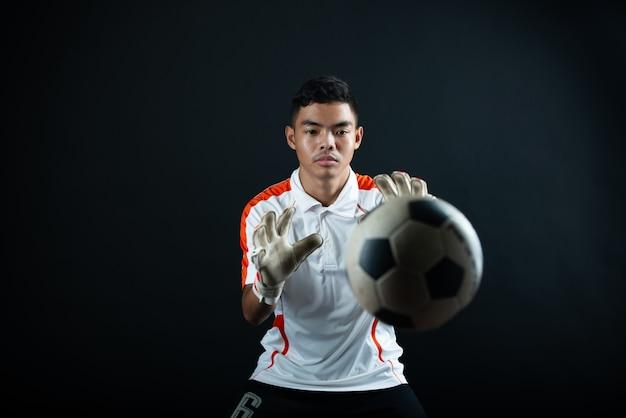 Giovane uomo di calcio del portiere isolato della squadra di calcio dell'accademia