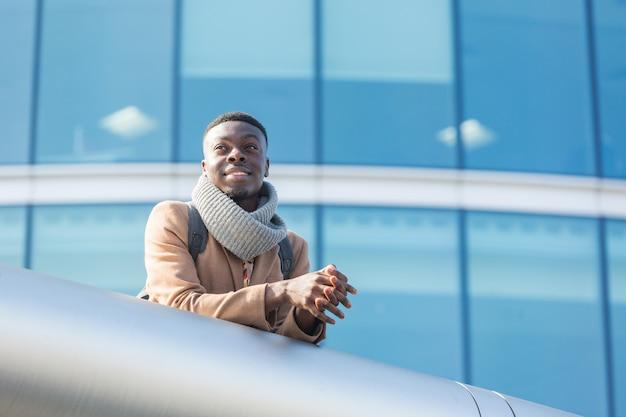 Giovane uomo di colore a londra con edificio moderno