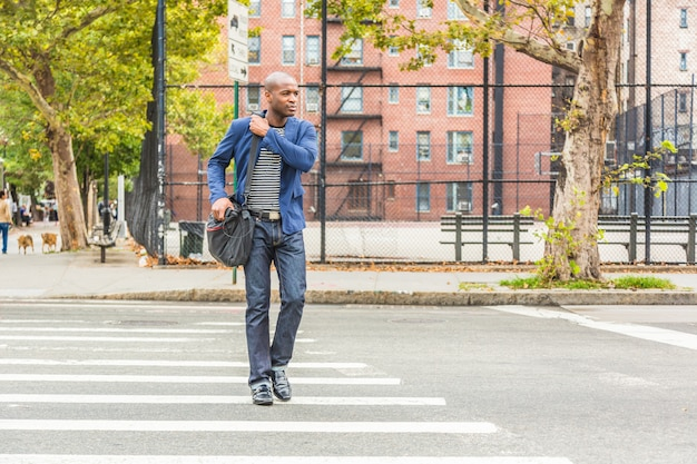 Giovane uomo di colore a new york, attraversando la strada