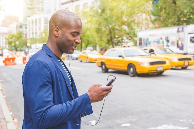 Giovane uomo di colore a new york guardando il suo telefono