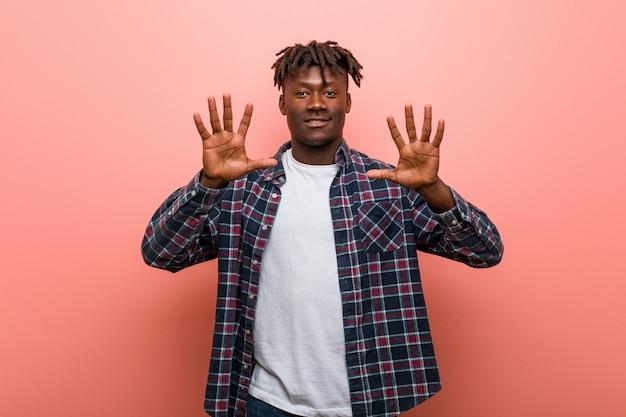 Giovane uomo di colore africano che mostra numero dieci con le mani.
