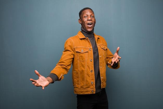 Giovane uomo di colore afroamericano che esegue opera o canta a un concerto o spettacolo, sentendosi romantico, artistico e appassionato contro il muro del grunge