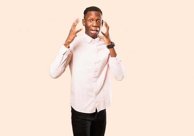 Giovane uomo di colore afroamericano che grida con le mani in alto nell'aria, sentendosi furioso, frustrato, stressato e turbato contro la parete beige