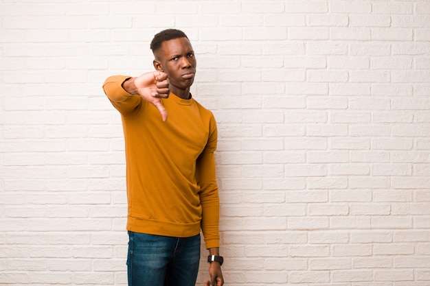 Giovane uomo di colore afroamericano che mostra i pollici giù