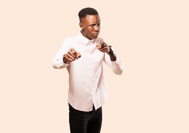 Giovane uomo di colore afroamericano che punta in avanti con entrambe le dita e l'espressione arrabbiata, che ti dice di fare il tuo dovere contro il muro beige