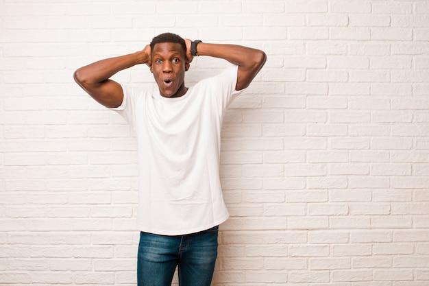 Giovane uomo di colore afroamericano che sembra eccitato e sorpreso, a bocca aperta con entrambe le mani sulla testa, sentendosi come un fortunato vincitore sul muro di mattoni