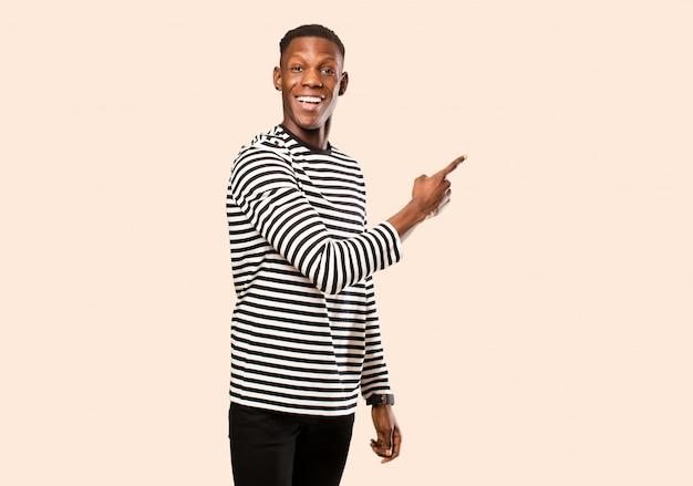Giovane uomo di colore afroamericano che sembra eccitato e sorpreso che punta di lato e verso l'alto per copiare lo spazio sulla parete beige