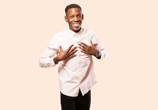 Giovane uomo di colore afroamericano che sembra felice, sorpreso, orgoglioso ed emozionato, indicando se stesso sulla parete beige