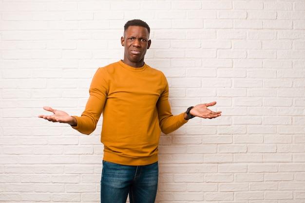 Giovane uomo di colore afroamericano che sembra perplesso, confuso e stressato, chiedendosi tra diverse opzioni, sentendosi incerto contro il muro di mattoni