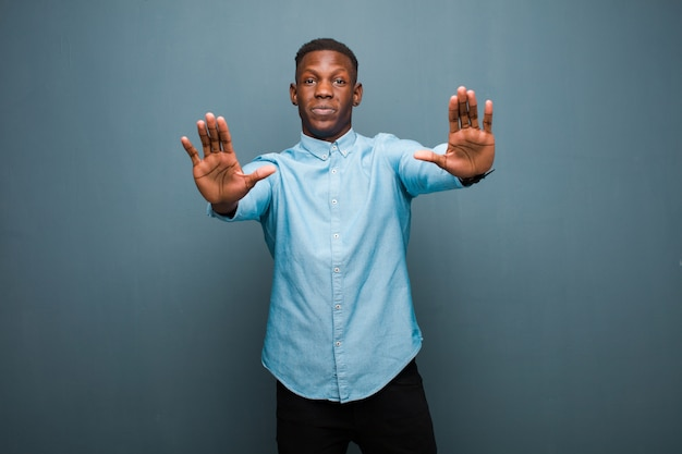 Giovane uomo di colore afroamericano che sembra serio, infelice, arrabbiato e scontento vietando l'ingresso o dicendo stop con entrambe le palme aperte