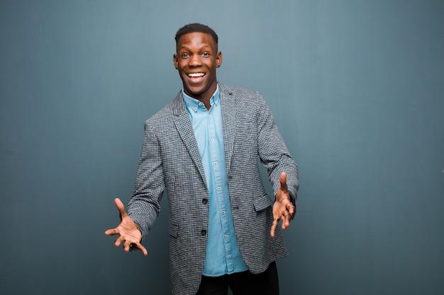 Giovane uomo di colore afroamericano che si sente felice, stupito, fortunato e sorpreso, come dire sul serio omg? incredibile contro il muro del grunge