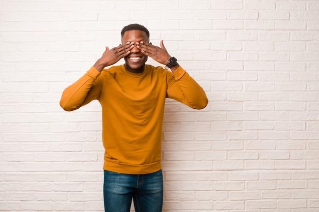Giovane uomo di colore afroamericano che sorride e si sente felice, coprendo gli occhi con entrambe le mani e aspettando un'incredibile sorpresa contro il muro di mattoni