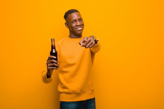 Giovane uomo di colore afroamericano contro la parete arancio che mangia una birra