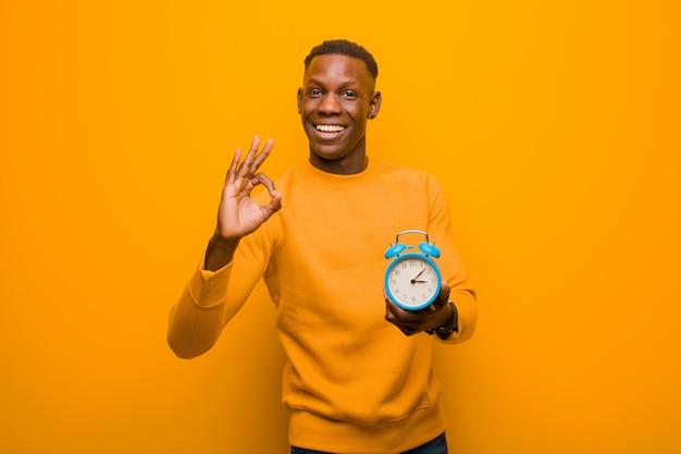 Giovane uomo di colore afroamericano contro la parete arancio che tiene una sveglia