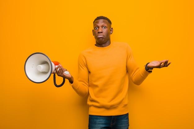 Giovane uomo di colore afroamericano contro la parete arancio con un megafono