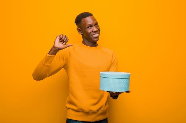 Giovane uomo di colore afroamericano contro la parete arancio con un regalo