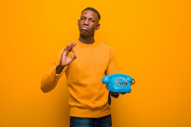 Giovane uomo di colore afroamericano contro la parete arancio con un telefono d'annata