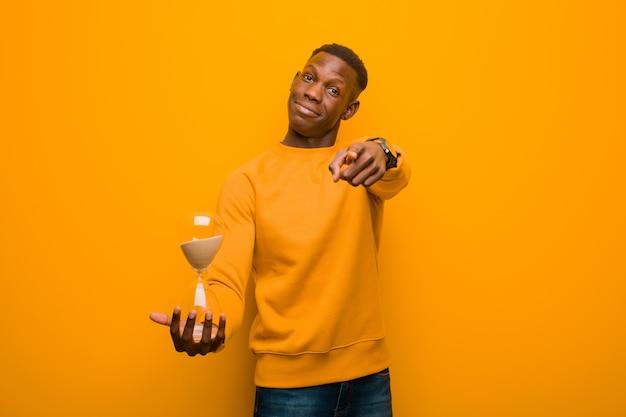 Giovane uomo di colore afroamericano contro la parete arancio con un temporizzatore dell'orologio della sabbia