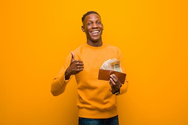 Giovane uomo di colore afroamericano contro la parete arancio, concetto dei soldi.
