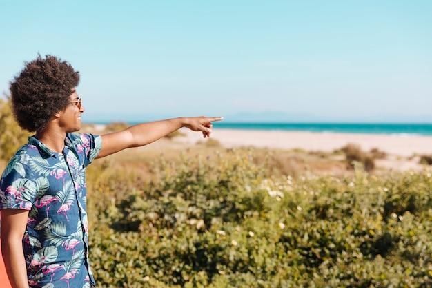 Giovane uomo di colore allegro che indica direzione sulla spiaggia