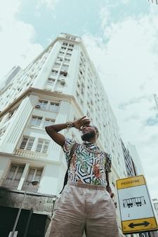 Giovane uomo di colore barbuto che cerca qualcosa nella città
