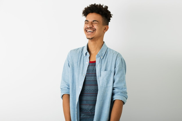 Giovane uomo di colore bello, che ride sinceramente, espressione del viso sorridente, stato d'animo positivo, emozione felice, isolato su sfondo bianco studio, gioventù afroamericana, stile hipster, studente