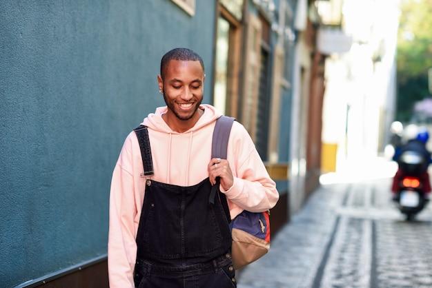 Giovane uomo di colore che cammina sorridendo per la strada.