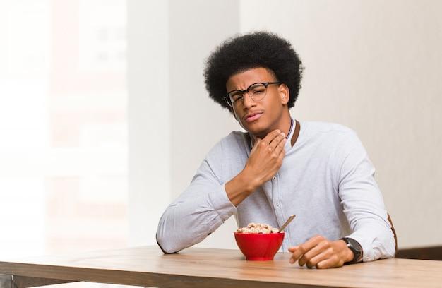 Giovane uomo di colore che fa colazione tossendo, malato a causa di un virus o infezione