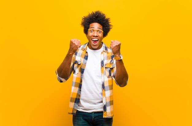 Giovane uomo di colore che grida trionfalmente, ridendo e sentendosi felice ed eccitato mentre celebra il successo contro la parete arancione
