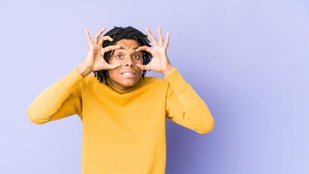 Giovane uomo di colore che indossa l'acconciatura rasta tenendo gli occhi aperti per trovare un'opportunità di successo.