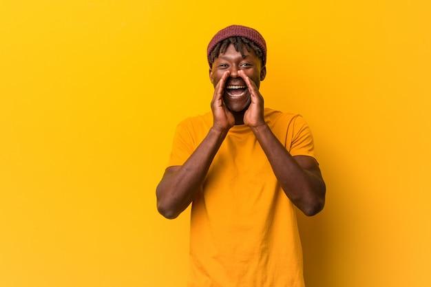 Giovane uomo di colore che indossa rasta su sfondo giallo che grida eccitato alla parte anteriore.