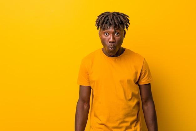 Giovane uomo di colore che indossa rastas sopra le spalle di scrollate di spalle gialle e gli occhi aperti confusi.