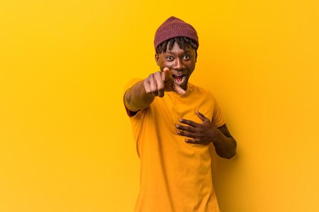 Giovane uomo di colore che indossa rastas su punti gialli con il dito di pollice di distanza, ridendo e spensierato.