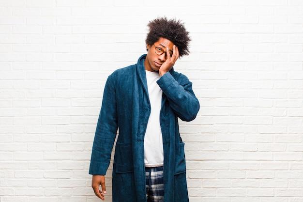 Giovane uomo di colore che indossa un pigiama con abito annoiato, frustrato e assonnato dopo un compito noioso, noioso e noioso, che tiene la faccia con il muro di mattoni a mano