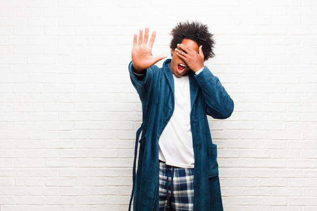 Giovane uomo di colore che indossa un pigiama con abito che copre il viso con la mano e mette l'altra mano in alto per fermare la fotocamera, rifiutando foto o immagini contro il muro di mattoni