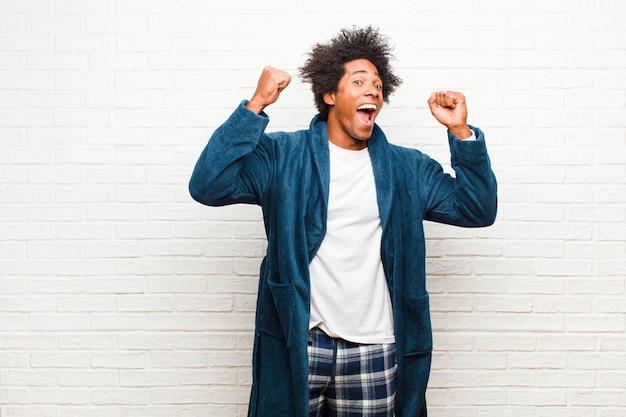 Giovane uomo di colore che indossa un pigiama con abito che grida trionfalmente, sembra eccitato, felice e sorpreso vincitore, festeggia contro il muro di mattoni