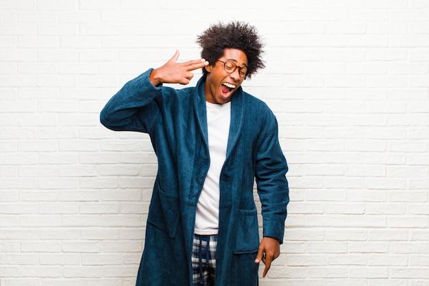 Giovane uomo di colore che indossa un pigiama con abito che sembra infelice e stressato, gesto suicida facendo segno di pistola con la mano, che punta alla testa