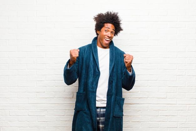 Giovane uomo di colore che indossa un pigiama con abito che sembra scioccato, eccitato e felice, che ride e celebra il successo, dicendo wow! contro il muro di mattoni