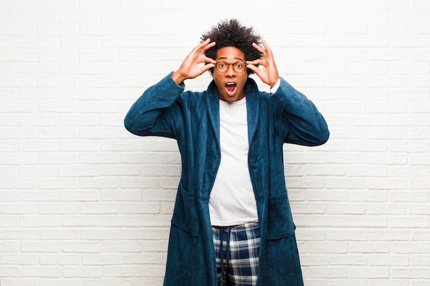 Giovane uomo di colore che indossa un pigiama con abito che sembra scioccato, stupito e sorpreso, con gli occhiali con uno sguardo stupito e incredulo