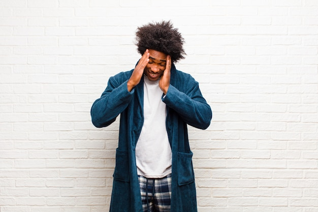 Giovane uomo di colore che indossa un pigiama con abito che sembra stressato e frustrato, che lavora sotto pressione con un mal di testa e turbato da problemi contro il muro di mattoni