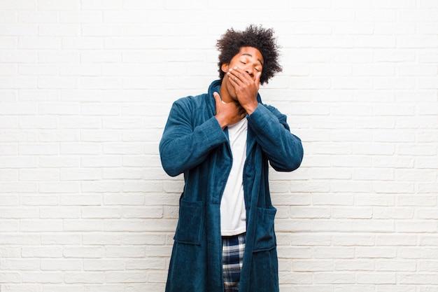 Giovane uomo di colore che indossa un pigiama con abito che si sente male con mal di gola e sintomi influenzali, tosse con la bocca coperta contro il muro di mattoni