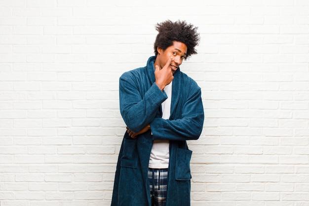Giovane uomo di colore che indossa un pigiama con abito che ti tiene d'occhio, non fidarsi, guardare e stare all'erta e vigile muro di mattoni