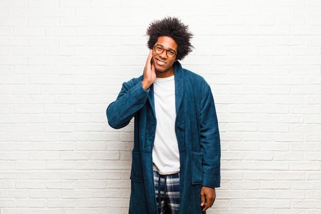 Giovane uomo di colore che indossa un pigiama con abito che tiene la guancia e che soffre di mal di denti doloroso, sentirsi male, miserabile e infelice, in cerca di un dentista contro il muro di mattoni
