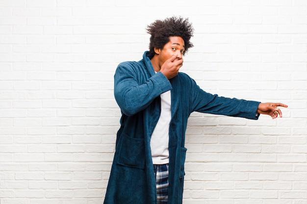 Giovane uomo di colore che indossa un pigiama con abito felice, scioccato e sorpreso, coprendosi la bocca con la mano e indicando lo spazio laterale della copia contro il muro di mattoni