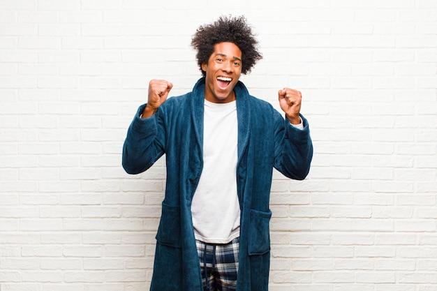 Giovane uomo di colore che indossa un pigiama con abito felice, sorpreso e orgoglioso, che grida e celebra il successo con un grande sorriso sul muro di mattoni