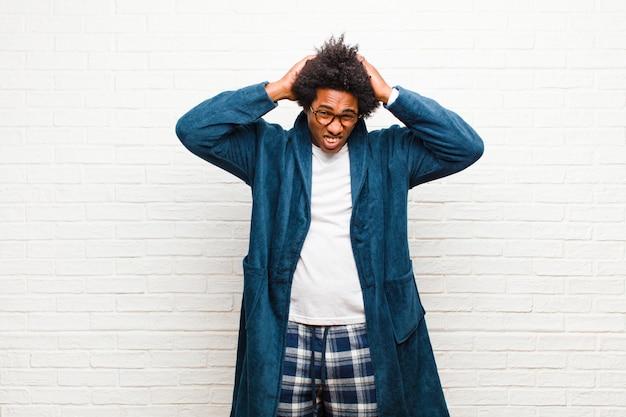 Giovane uomo di colore che indossa un pigiama con abito frustrato e infastidito, stufo e stanco del fallimento, stufo di compiti noiosi e noiosi contro il muro di mattoni