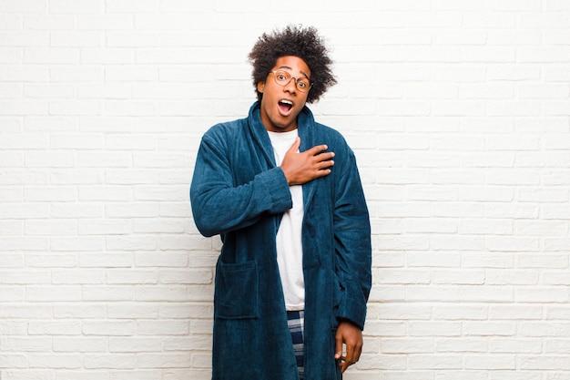 Giovane uomo di colore che indossa un pigiama con abito sentendosi scioccato e sorpreso, sorridendo, prendendosi per mano, felice di essere quello o mostrando gratitudine