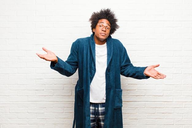 Giovane uomo di colore che indossa un pigiama con un abito perplesso e confuso, incerto sulla risposta o decisione corretta, cercando di fare una scelta