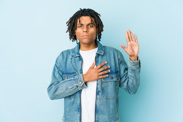 Giovane uomo di colore che indossa una giacca di jeans che presta giuramento, mettendo la mano sul petto.